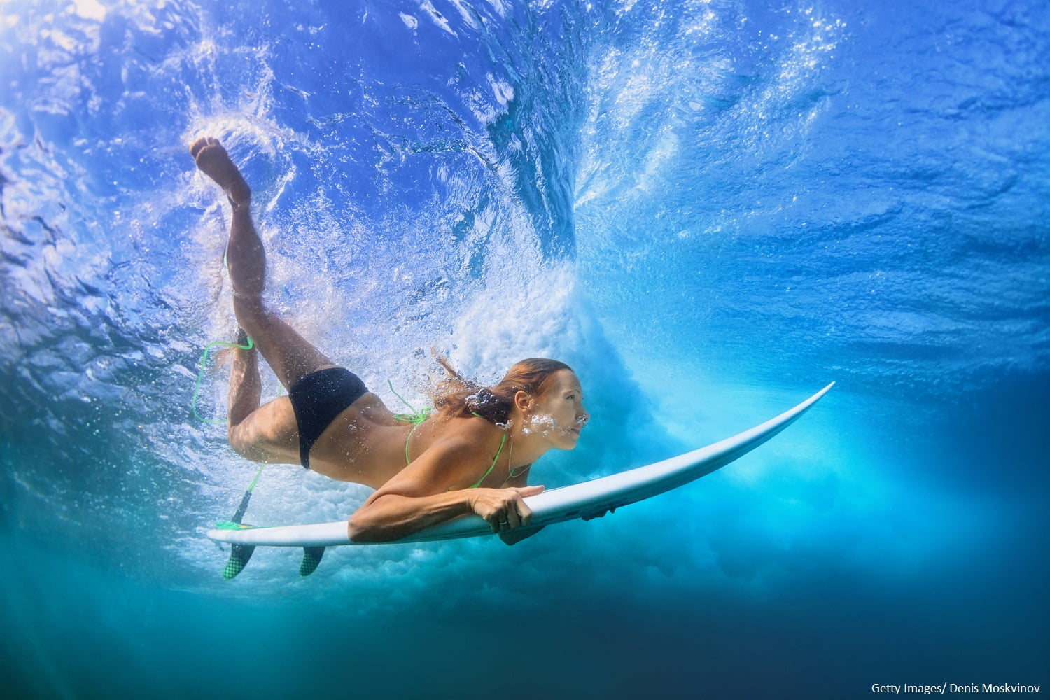 Girl diving underwater with a surfboard at one of the best Maui surfing spots