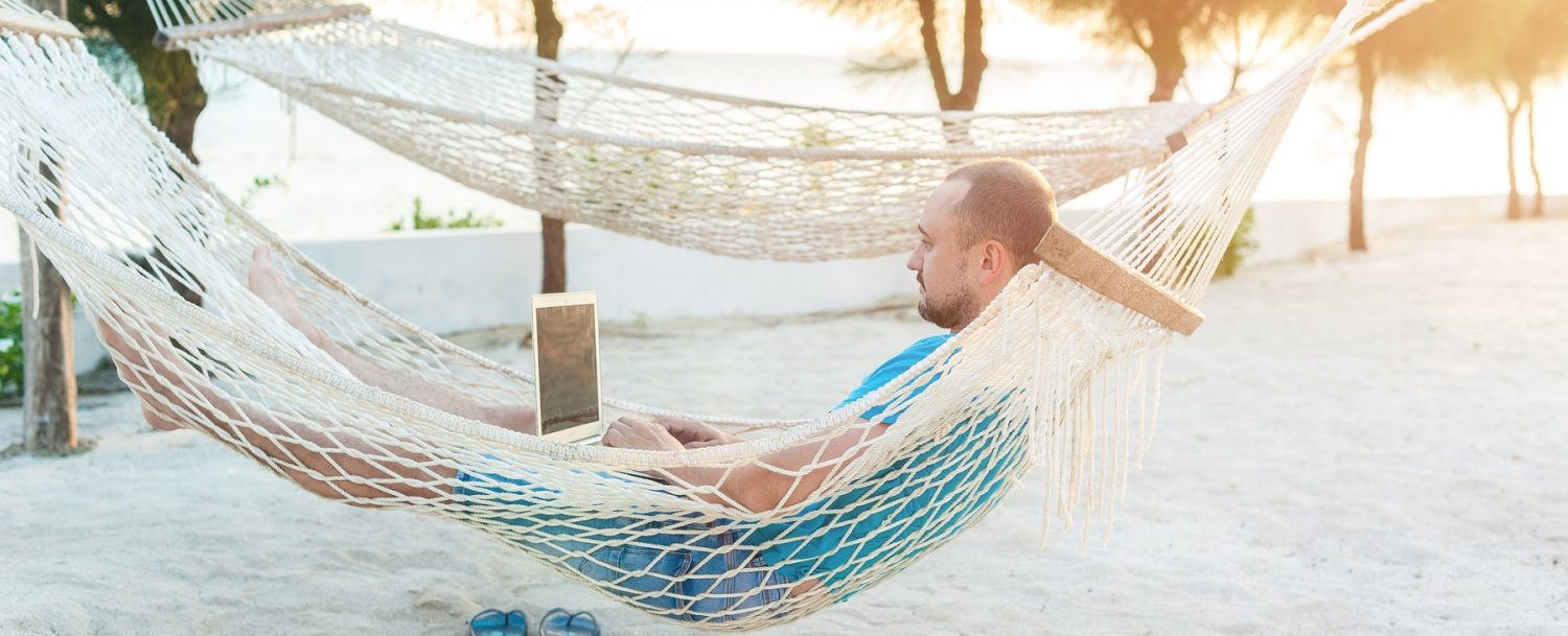 Man in hammock working on his computer during a Maui business trip